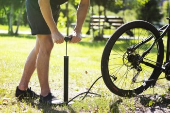 man pumping bicycle tyre, performing bicycle maintenance